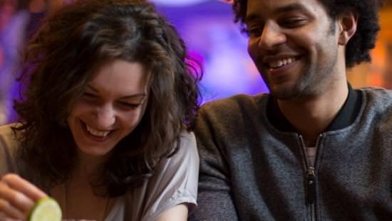 Un homme et une femme sont assis ensemble dans une conversation autour d'un verre