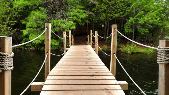 A wooden bridge crosses a creek to connect hiking trails