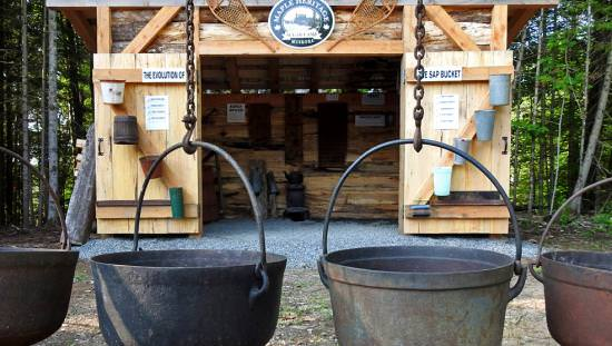 Four large maple syrup pots hang in front of a sugar shack