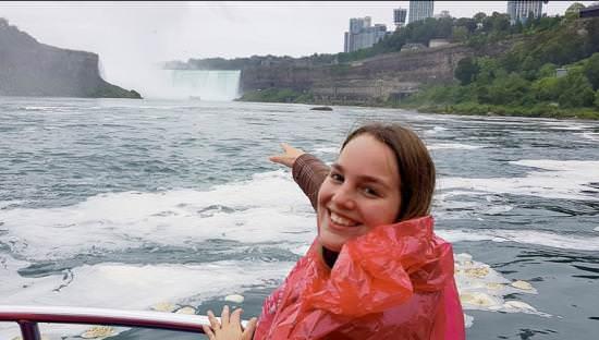Une jeune fille sur un bateau qui pointe en direction du paysage de Niagara Falls