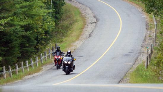 Two motorcyclists ride down a scenic highway