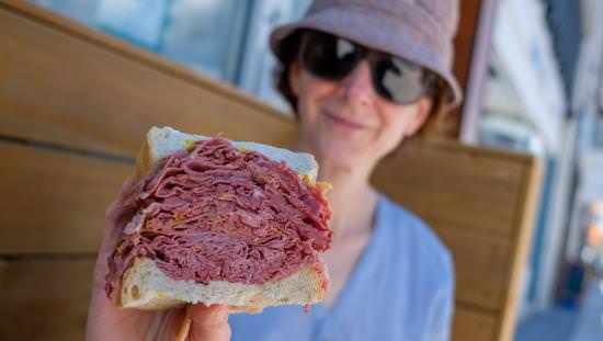 Woman displaying her meat sandwich to the camera