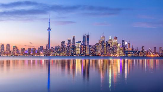 The Toronto skyline in the evening reflects on a body of water