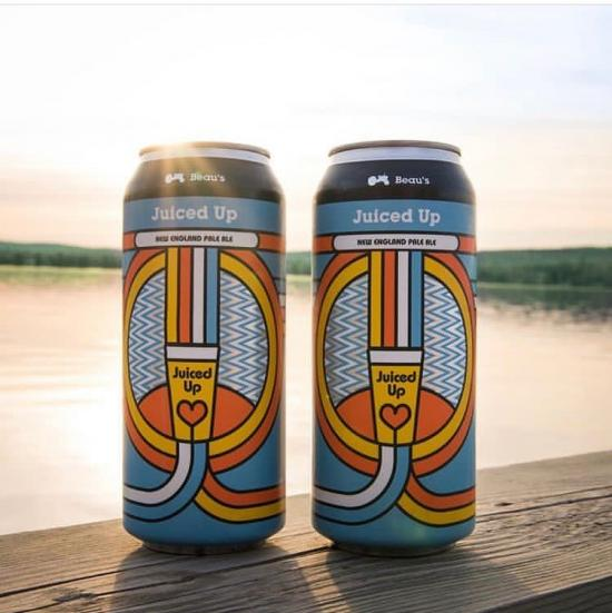 Close up of two colourful Beau's Juiced Up beer cans sitting on a table with the lake in the background