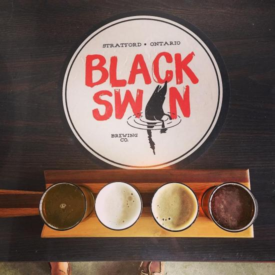 Overhead shot of a flight of four varying colours of beers, in front of the Black Swan logo