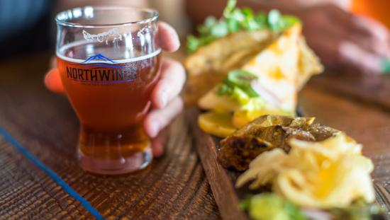 Close up of a man's hand holding a beer, next to a plate of food