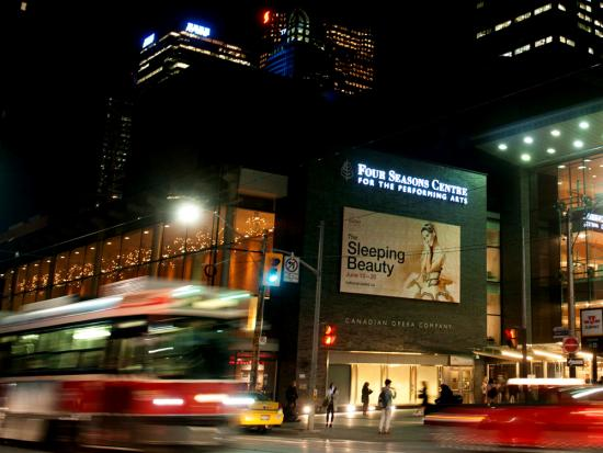 A streetcar and traffic passes in front of a large poster for The Sleeping Beauty ballet in Toronto