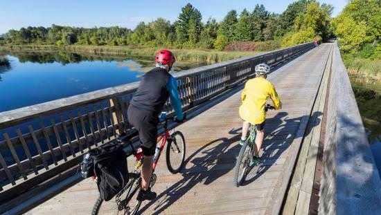 Deux personnes en vélo sur un pont en bois au-dessus d'un cours d'eau qui se dirigent vers un sentier dans la forêt.