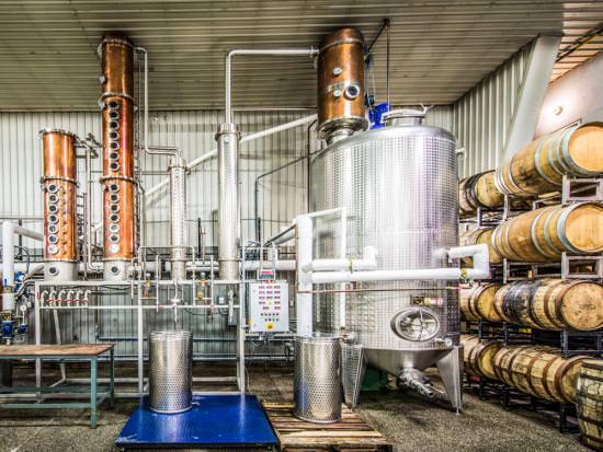 Machines brillantes et vieux tonneaux dans une distillerie en activité