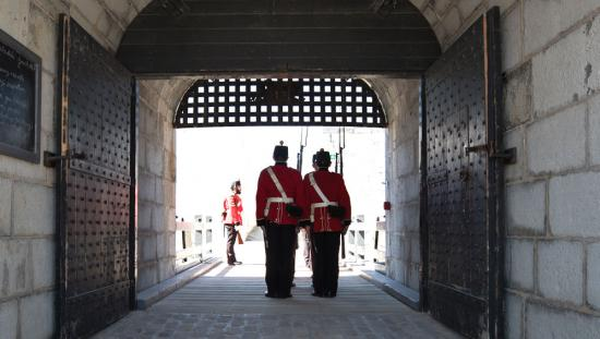 Two soldiers stand on guard at the gateway of a fort