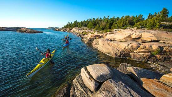 Trois personnes qui pagaient le long d'un lac près d'un terrain rocheux contenant des arbres.