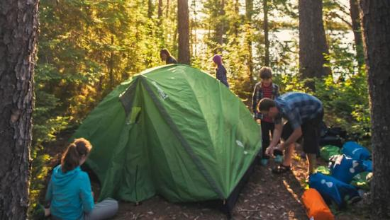 A family of 5 pitching their tent in between mature trees.