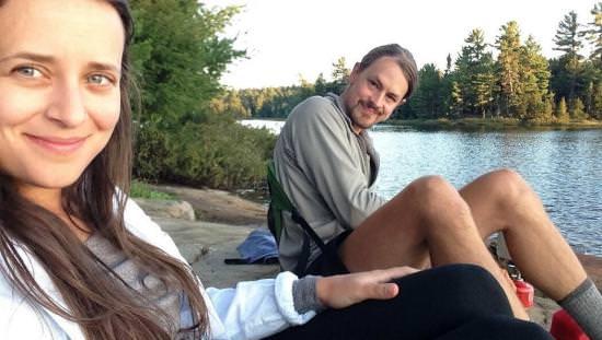 Un jeune couple sourit à l'objectif et met en valeur l'arrière-plan constitué d'un cours d'eau entre les arbres.