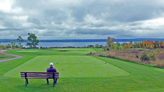 Un homme est assis sur un banc donnant sur un terrain de golf