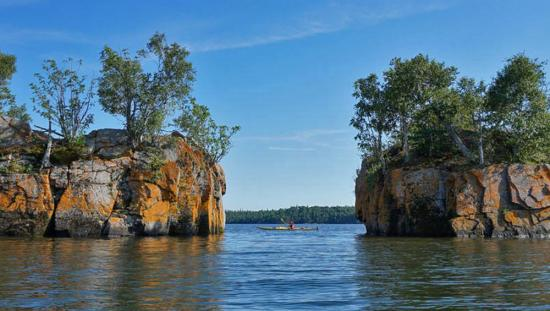 A person seen kayaking on a lake in between 2 large cliffs with trees on the top.