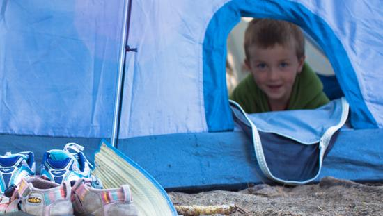 A little boy peers out from a blue tent
