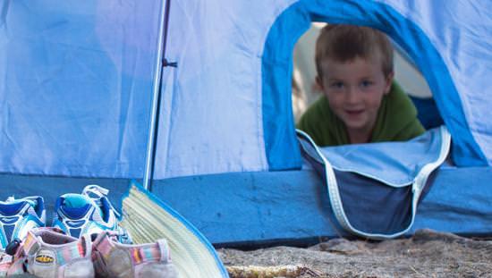 Un petit garçon regarde d'une tente bleue