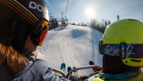 Deux personnes entièrement équipées pour le ski alpin sur un remonte-pente durant une froide journée ensoleillée.