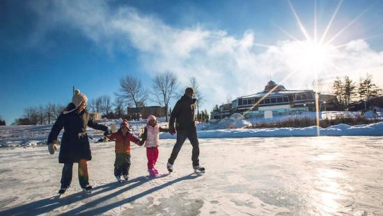 A family of 4, holding hands skating on an outside rink on a cold sunny day.