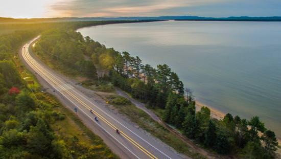 Trois motocyclistes roulent sur une autoroute le long d'un immense lac