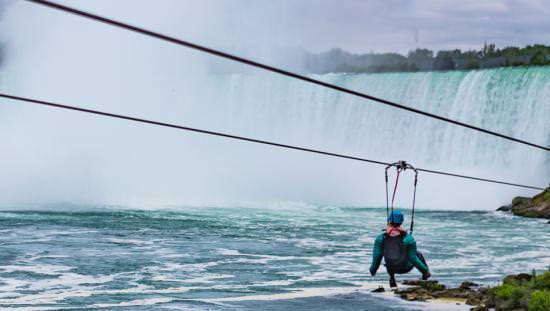 une personne monte une tyrolienne devant les chutes du Niagara