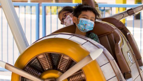 Two children enjoy a ride at an amusement park