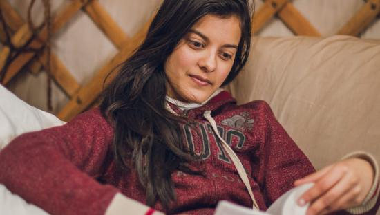 A woman relaxes reading a book in a yurt