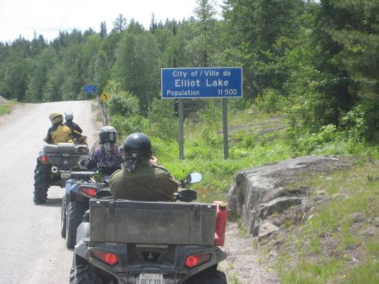 A row of riders on ATVs cruise along a trail