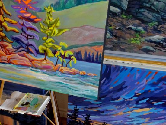 The work station of a local artist featuring colourful landscape painting
