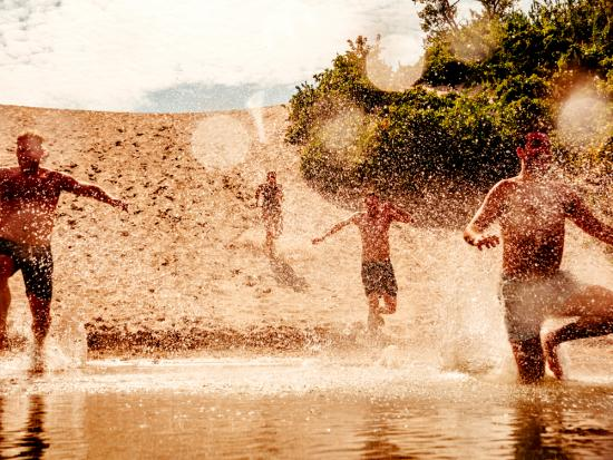 Four men run down a sandy beach into the lake