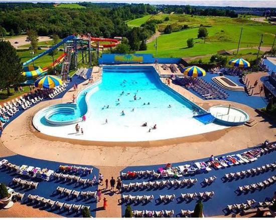 Vue à vol d'oiseau de personnes profitant d'une grande piscine à vagues, entourée de chaises longues et de deux parasols bleus et jaunes