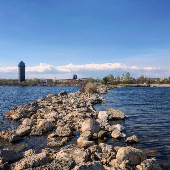 Du point de vue de se tenir sur une péninsule rocheuse entourée d'eau en regardant la marina sur le rivage