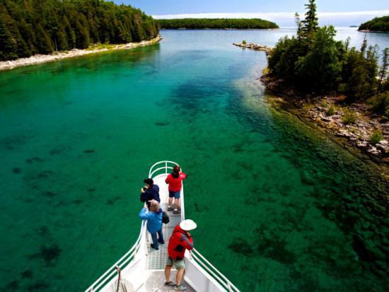 Des aventuriers profitent de la vue à la proue d'un bateau, qui glisse sur les eaux limpides du Bouclier canadien