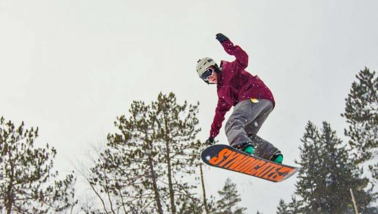 A snowboarder in mid-air while riding down a ski hill