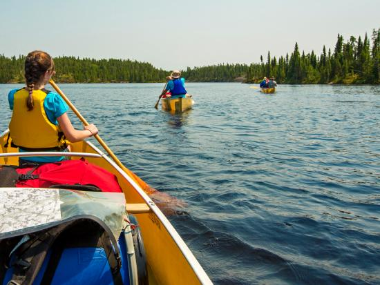 Three yellow canoes set out across a large lake