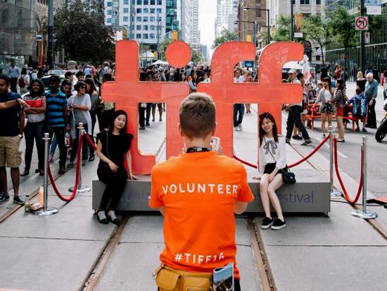 A TIFF volunteer takes a photo of festival attendees