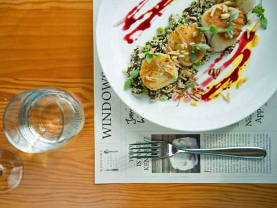 Assiette de pétoncles prêtes à manger, posée à côté d'une fourchette et d'un verre d'eau sur une table.