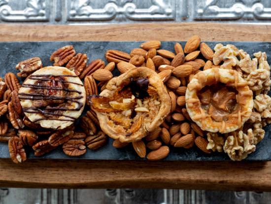 Trois délicieuses tartes au beurre posées sur une planche de charcuterie entourées de noix