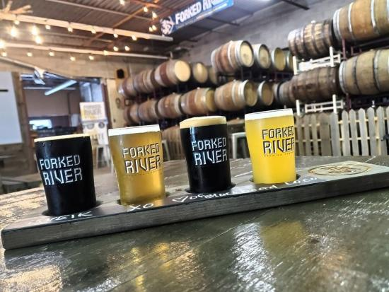 A flight of 4 beers featuring dark and pale ales with barrels in the background