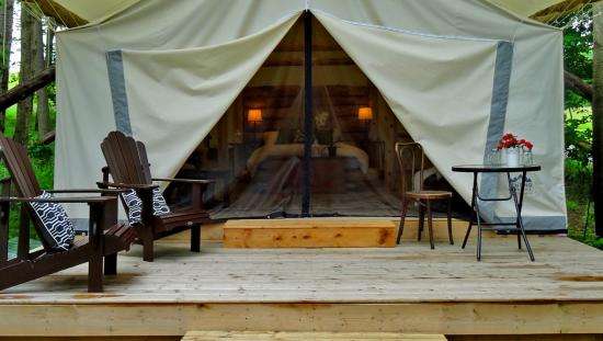 A glamping site with seating outside and the front tent folded back