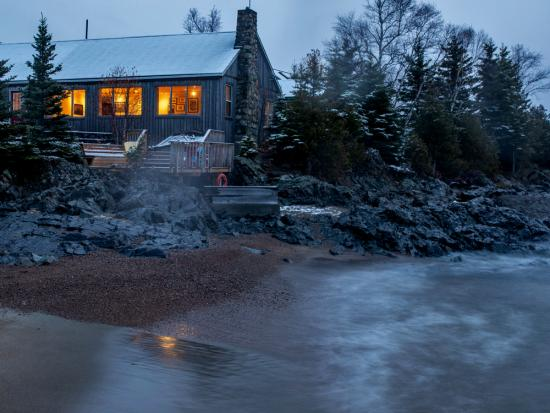There's a warm glow in the windows of a cozy cabin perched on the edge of a lake