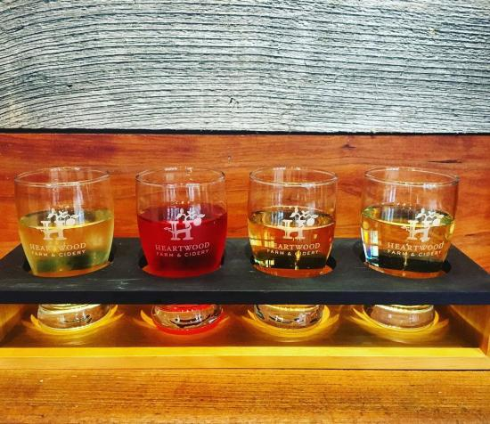 A flight of 4 ciders sitting on a wood table