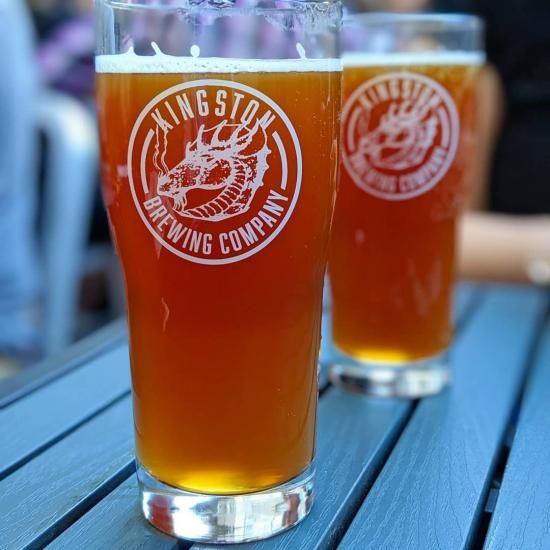 Two glasses of beer resting on a table.  One glass is close up in the foreground, one glass is in the background.