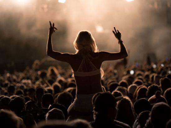 A concertgoer enjoys the view from above the crowd as she rests on her partner's shoulders