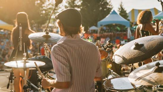 A band performs on stage in front of an audience at a summer music festival