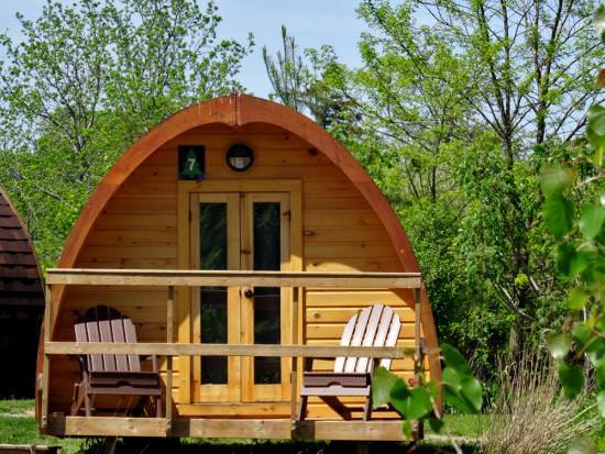 Une petite cabane de glamping en bois couverte d'un dôme