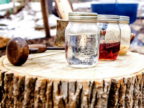 Three mason jars of maple syrup sit on a wooden table