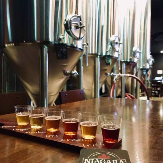 Un vol de six échantillons de bières est assis sur une table au premier plan, tandis que l'équipement de brassage est affiché à l'arrière-plan