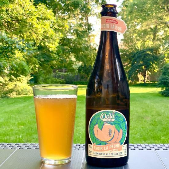 A refreshing glass of beer beside a tall bottle of beer in a backyard setting
