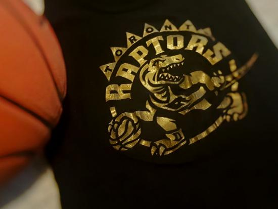 A basketball and a t-shirt with the Toronto Raptors logo